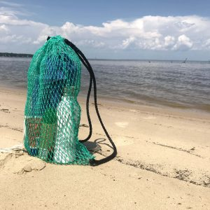 The Osprey Litter Gitter Backpack is filled with beach items and sitting on the beach. The bag features green mesh with black handles and a cinch top to close it.
