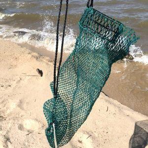 The empty Osprey Litter Gitter bag is being held with the beach in the background. It is a bag made of green mesh material with black handles and a cinch bottom, to allow to release litter. It has an opening that stays open so you can easily put litter in it while walking or jogging.