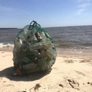 The Osprey Reusable Recycle bag is shown on the beach with empty recyclable bottles inside. It is made of a green mesh material with black handles that cinch the top shut.