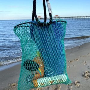 The Osprey tote bag is being held with the beach in the background. The bag contains beach items, including sunscreen and a towel. The bag is made of green mesh material with black rope handles.