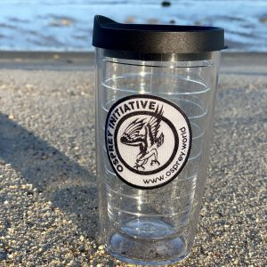 A clear tervis tumbler is positioned on the beach. The tumbler features a black and white Osprey logo with a black lid.