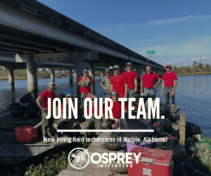 The Osprey Initiative workers are pictured at the end of a pier under a bridge and overlooking the water. Some team members are on the pier and others are in boats. Bagged trash and litter are in front of the team.