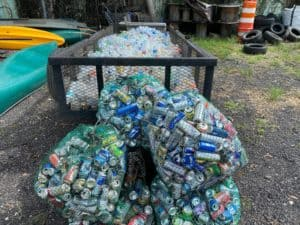 Five green mesh bags are shown holding a variety of aluminum cans. They are pictured in front of a black trailer completely full of plastic bottles. All items were picked up from litter cleanups and are heading to recycling.